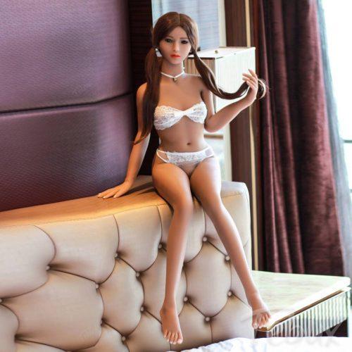 Skinny sex doll sitting wearing white lingerie
