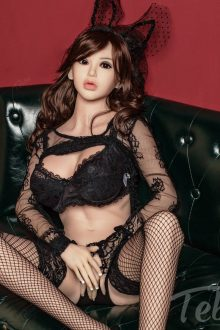 Love Sex Doll in a sexy black outfit sitting on a black bench looking seductively at the camera