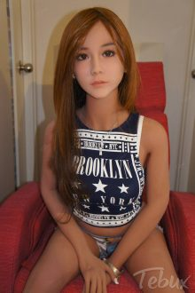 brunette Best TPE Sex Doll in a blue tanktop sitting on red chair