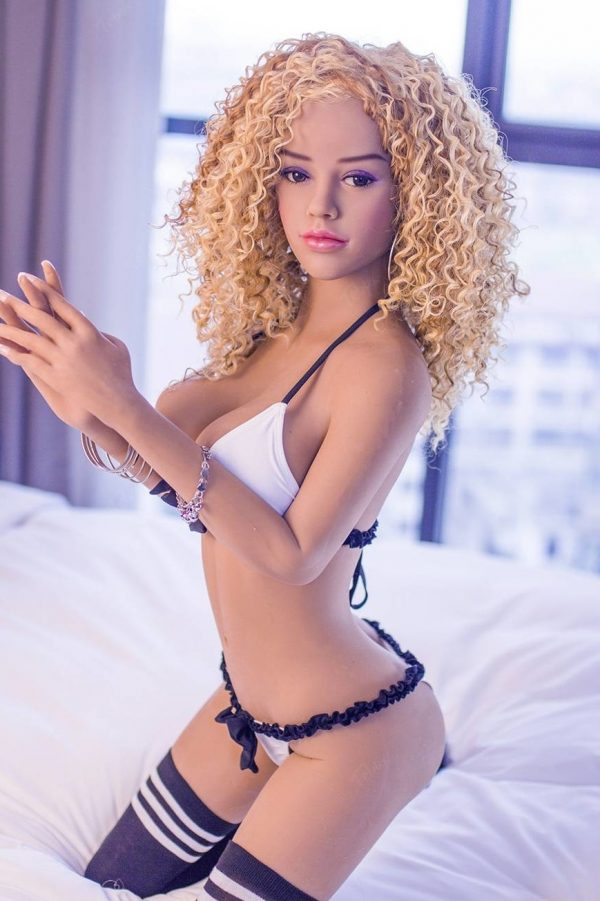 curly blonde Small Sex Dolls in white bikini and striped kneesocks sitting on bed