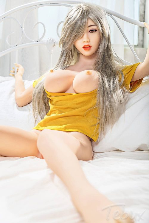 gray haired Small Silicone Sex Doll flashing her boobs above yellow shirt