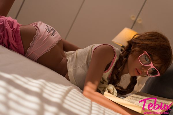 red head sex doll lying in bed reading a book