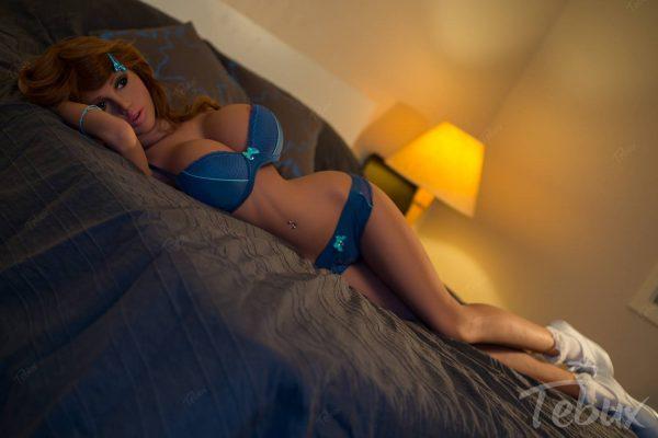 Big breast sex doll Erika lying on bed