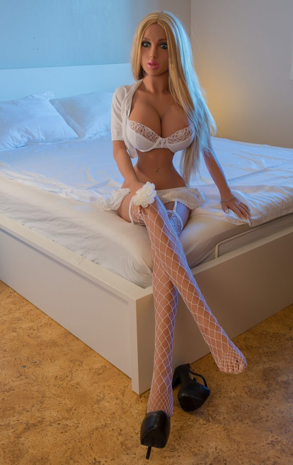 Blonde sex doll Kenley sitting on bed in lingerie