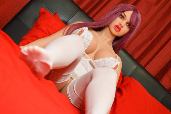 Busty sex doll lying on bed