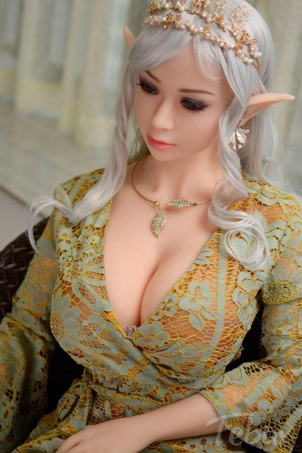 Elf sex doll Holly sitting wearing green dress