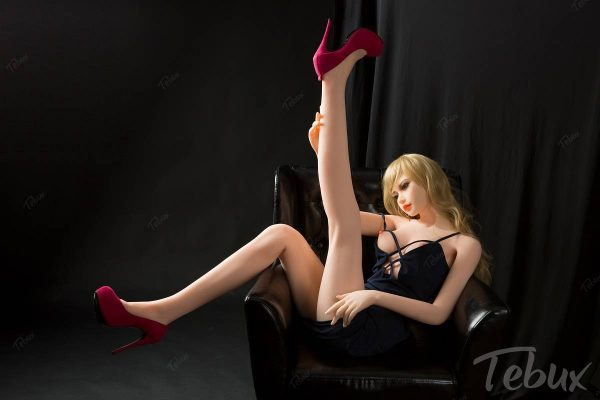 Flat chested sex doll Elora sitting wearing a black dress
