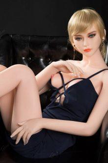 Flat chested sex doll Elora sitting wearing a black dress