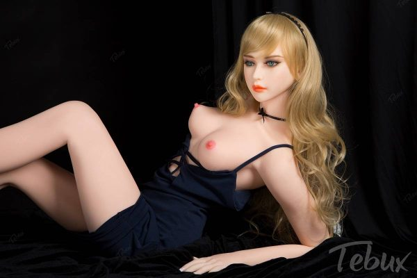 Flat chested sex doll Elora lying with a black dress on