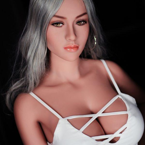 Life-like sex doll sitting wearing white dress