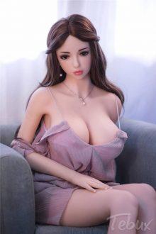 Life sized sex doll Marissa sitting on chair wearing dress