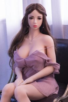 brunette Life Sized Sex Doll in short brown dress sitting on black chair