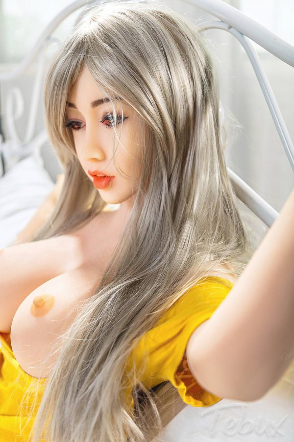Small silicone sex doll lying down topless