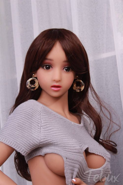 Tiny sex doll standing in grey top