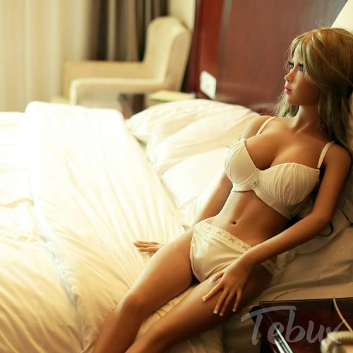 Tiny sex doll wearing lingerie on bed