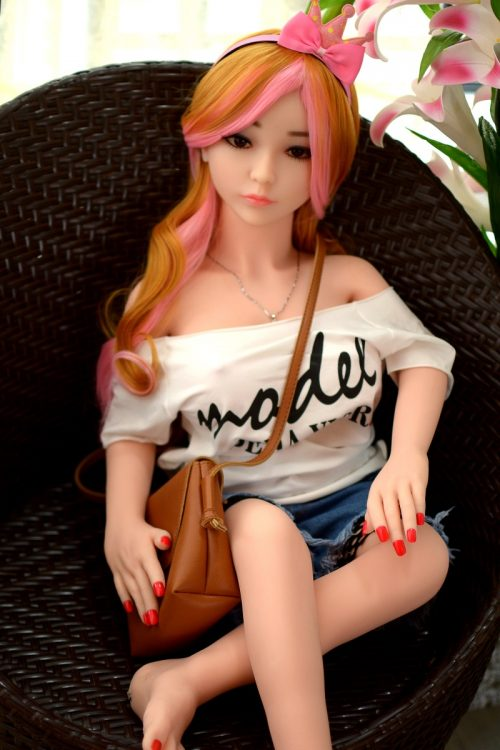 Short Sex Doll with colorful hair sitting in a brown chair