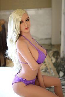 blonde BBW Love Doll in purple bikini sitting on bed