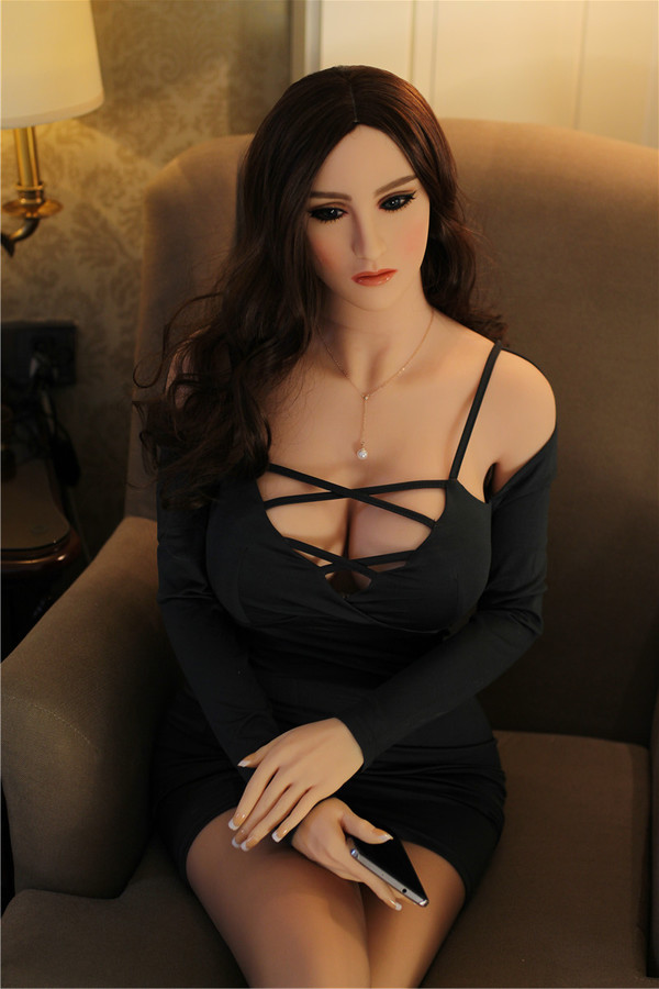 brunette sex doll in black dress with phone in hand