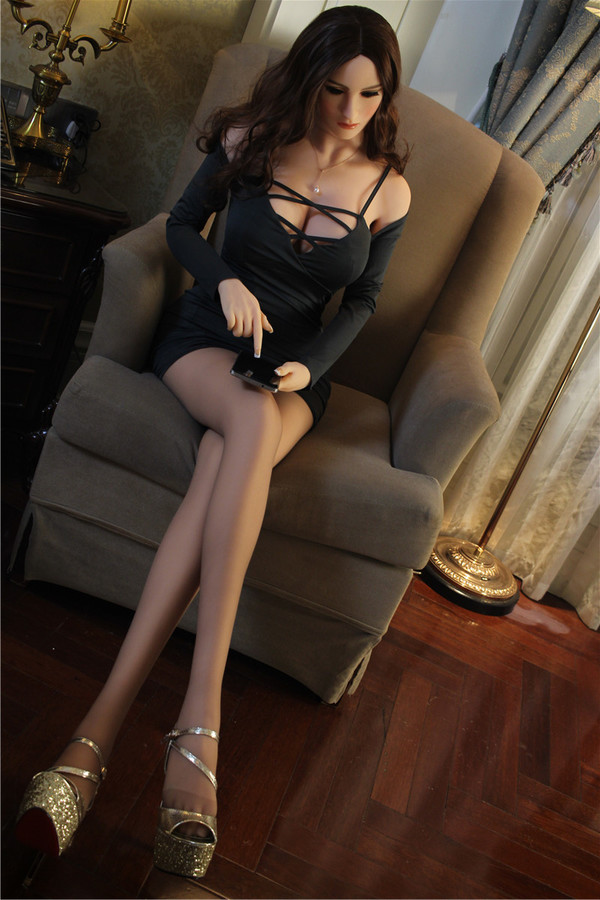 brunette sex doll in black dress sitting in a chair